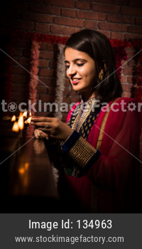 Pretty Young Indian girl arranging Diyas on Diwali Festival Night