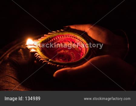 Hand holding diwali diya, closeup