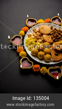 Diwali Rangoli or design made using Indian snacks/sweet and diya or lamp and flowers