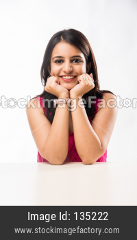 Indian girl sitting at table with resting chin on hands