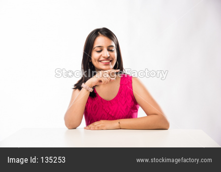 Indian girl sitting at table and pointing finger / presenting something