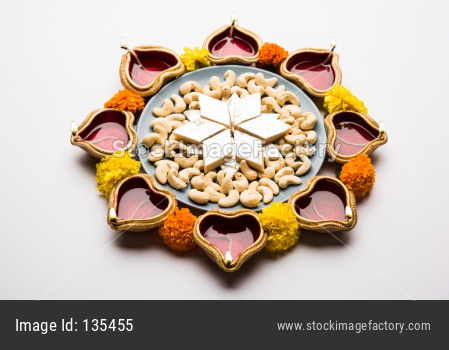 Diwali food Rangoli using Kaju Katli sweet, flower and diya