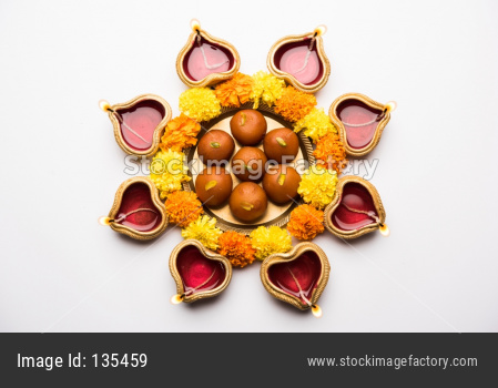 Diwali Rangoli using Diya, flowers and sweets