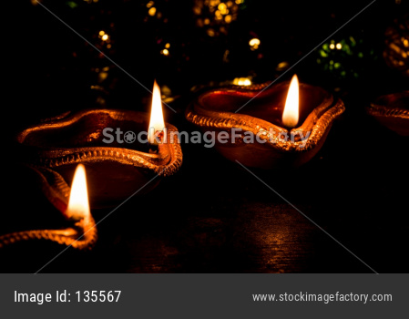 Diwali diyas at night with flowers, lighting series and gifts
