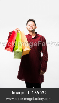 Indian/asian man in ethnic wear with shopping bags, standing isolated over white background