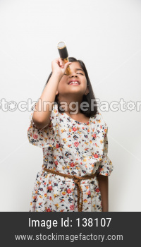 Cute little girl using stretch telescope and looking up in the sky