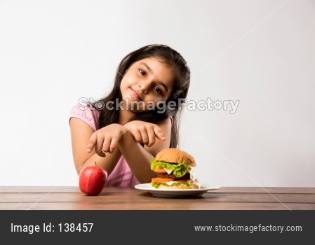 Llittle girl confused with Burger and apple