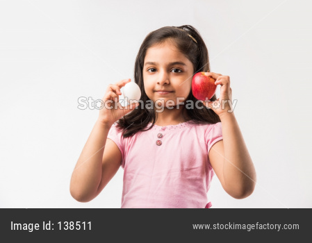 Small Girl eating egg and apple