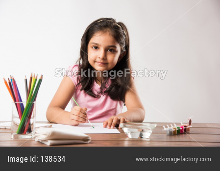 Cute little girl drawing with pencils and colours