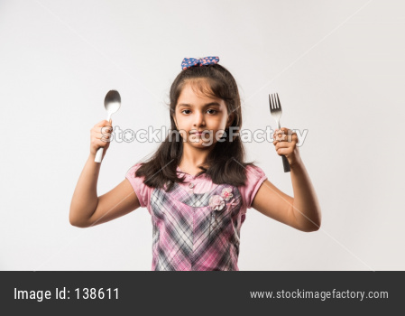 Small Girl showing spoon and fork over white background