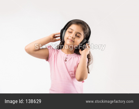 Cute Indian/asian small girl listening to music on wireless headphones isolated on white