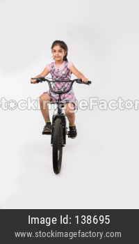 Cute little Indian/asian girl riding on bicycle, isolated over white background
