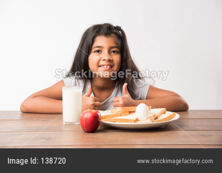Small Girl eating bread-jam with egg and milk