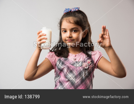 Cute little girl drinking Milk from glass