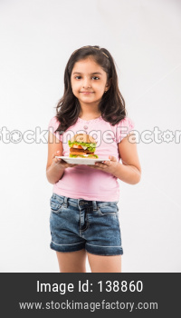 Cute little girl eating burger