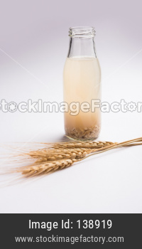 Barley water in glass with raw and cooked pearl barley wheat/seeds