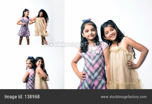Playful and pretty Indian/asian little sisters or friends in playful mood, hugging, dancing, pushing each other. Isolated over w