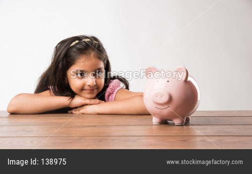 cute little Indian/asian girl holding pink piggy bank and books while standing isolated over green background