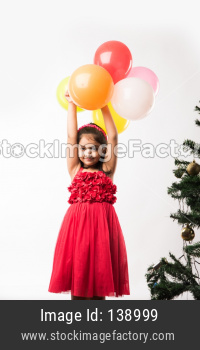 cute little indian/asian girl with colourful balloons or gubbare in Hindi, over white or red background