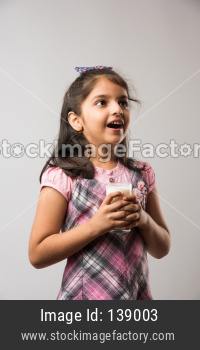 Cute little girl drinking Milk from glass