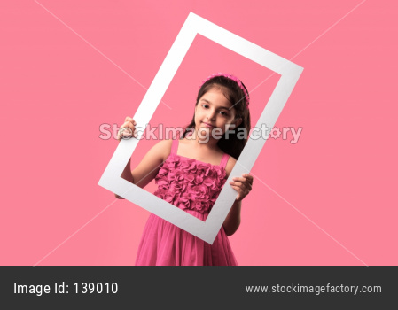 small Indian/asian girl holding and looking through empty frame, isolated over plain background