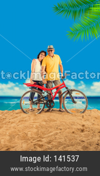 senior couple riding bicycle at beach