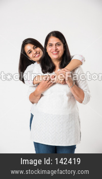 Old mother with young daughter, standing isolated over white background