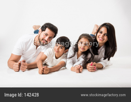 Young family lying on white looking at camera