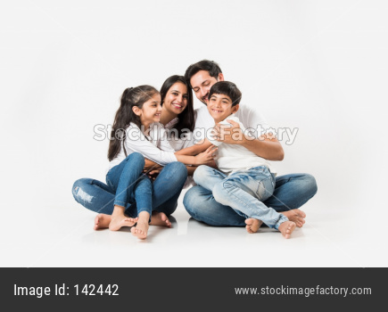 Young family sitting isolated over white