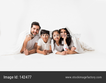 Indian parents with children lying under bed cover