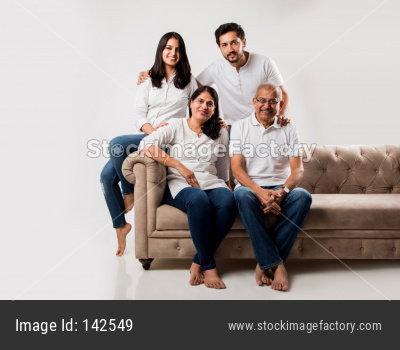 Indian/asian family sitting on sofa or couch over white background
