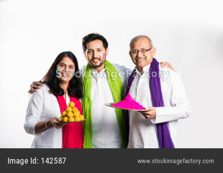Family playing holi, young adult with parents posing for photo on Holi festival