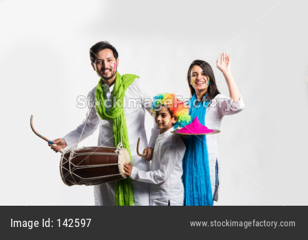 young couple with kid celebrating holi festival