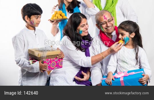 Family eating sweet laddu on Holi festival