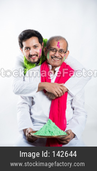 Indian father-son celebrating holi with colours. isolated over white background