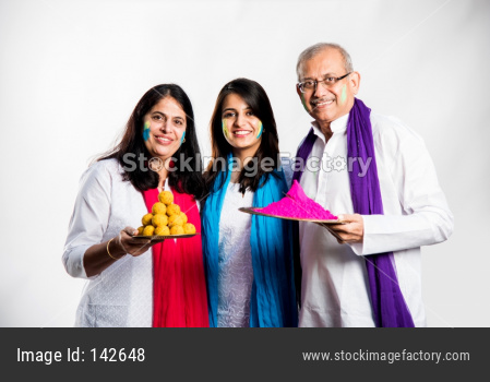 Family playing holi, young adult girl with parents posing for photo on Holi festival