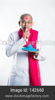 Senior man playing Holi with plate full of colours, keep silence pose