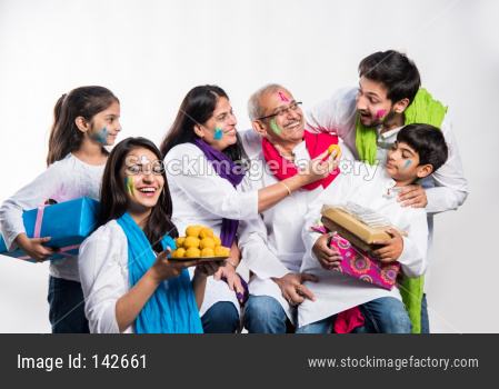 Family eating sweet laddu on Holi festival