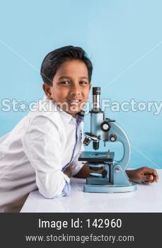 Cute little school kid studying science