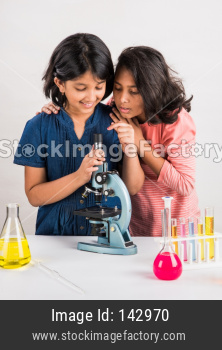 Cute little school girls studying science