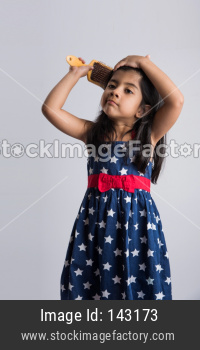 Indian cute girl combing hair with brush