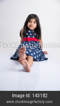 Indian cute girl sitting on white floor