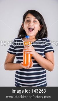 Cute little girl drinking mango juice or cold drink / beverage