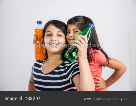 Cute little girls drinking mango juice or cold drink / beverage