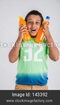 Cute little boy drinking mango juice or cold drink / beverage