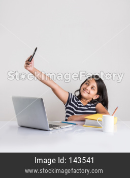 Indian school girl using smartphone while studying with laptop and books