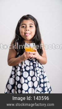 Cute little girl drinking mango juice or orange juice or cold drink