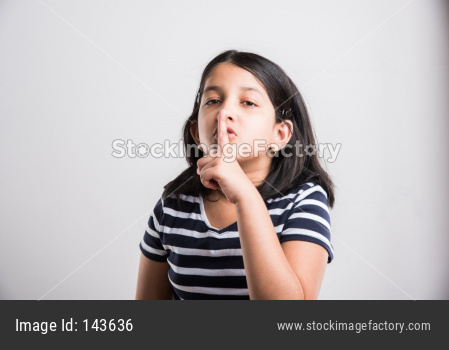 Cute little indian showing keep silence sign