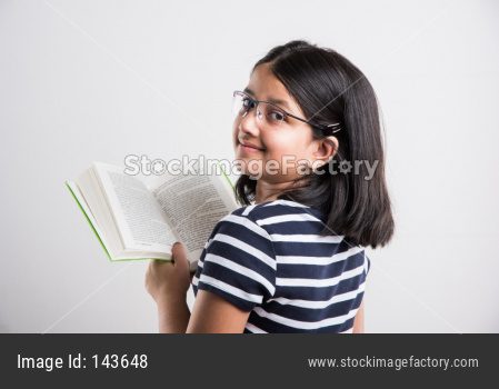 Indian school girl studying with book while standing