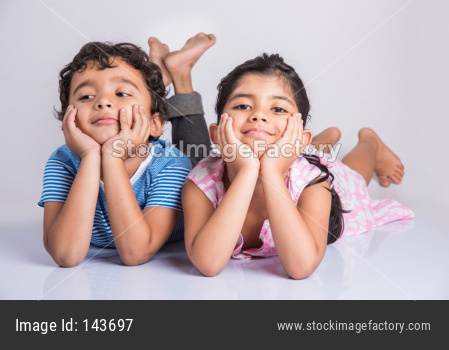 Cute little indian brother and sister / siblings sitting on floor